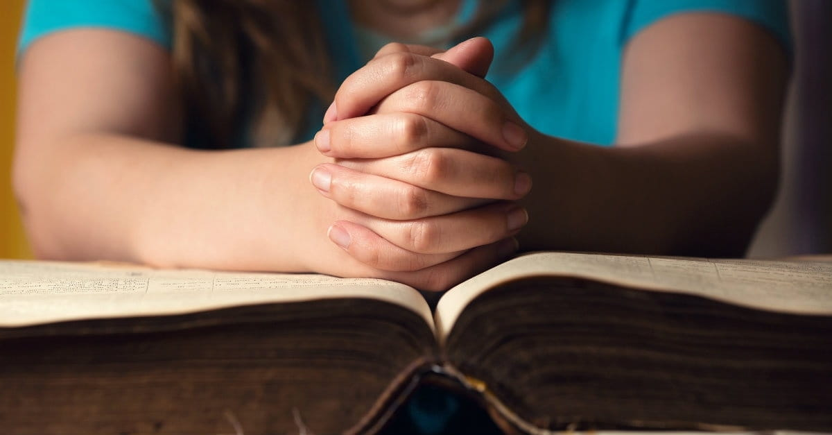 33418-praying-over-bible-1200.1200w.tn